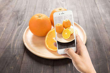 Taking photo of fresh oranges on wooden dish, fresh fruits on wo