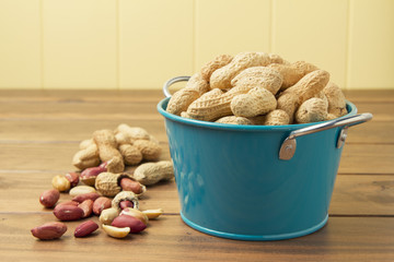 Some peanuts in a turquoise bucket on a wooden table.