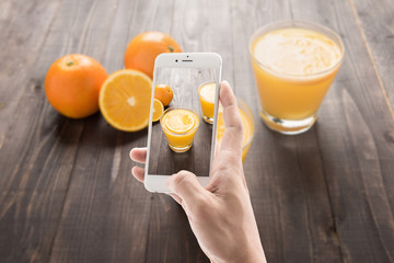Taking photo of orange juice and orange on the wooden background