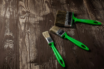 Three brushes for painting on a dark wooden table.