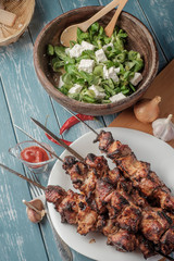 Shashlik with salad on the wooden table.