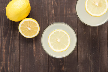 Top view lemonade with fresh lemon on wooden background