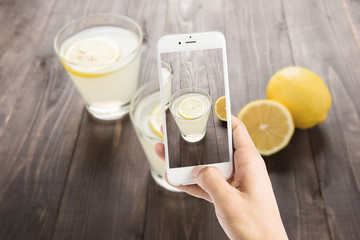 Taking photo of freshly squeezed lemon juice in glasses