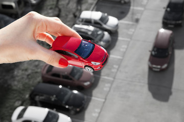 Dream to have a car. Hand holding a red toy car over parking.