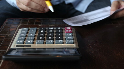 Business man accountant making calculations writing bills