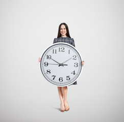 smiley woman holding big white clock