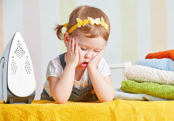 tired cute  baby girl housewife iron clothes iron, is engaged in