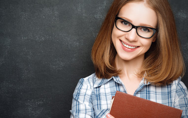 happy girl student with glasses and book from blackboard