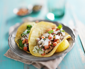 mexican authentic carnitas tacos with sour cream