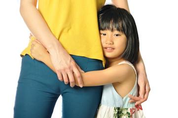 Asian little girl hugging mother's waist