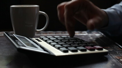 Business man typing on calculator drinking coffee, tea