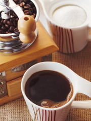 Manual coffee grinder, cup of coffee and sugar-bowl