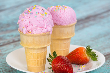 Strawberry ice cream with sprinkles in waffle cups