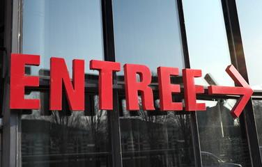 Entrée rouge avec flèche vers la droite sur façade vitrée.