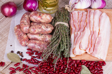 Red beans, thyme, sausages and bacon on wooden background