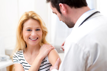 Young attractive woman being vaccinated