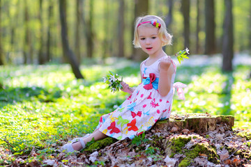 Adorable toddler girl enjoying sunny day in beautiful forest