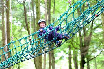 Happy boy climbing in adventure park