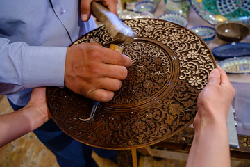 Craftsman carving patterns on the wooden plate