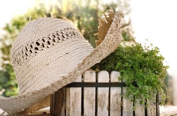 chapeau de paille sur petite jardinière en bois blanc