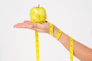 Woman holding apple with measuring tape