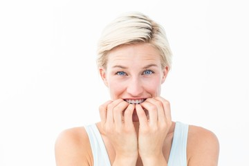 Nervous woman biting her nails looking at camera