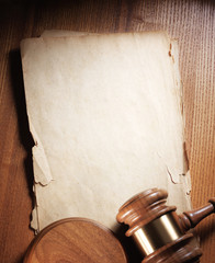Judge gavel and paper sheet on wooden background.
