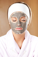 Young woman with clay skin mask on her face