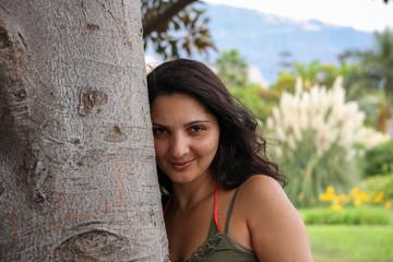 Frau lehnt an Baum in Natur
