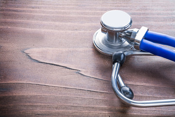 close up view head of stethoscope on vintage wooden board