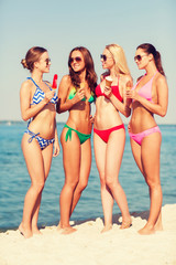 group of smiling women eating ice cream on beach