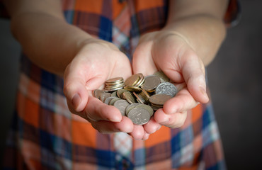 Hands holding coins. Selective focus.