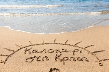 Hand made text in sand on a beach - Καλοκαίρι στη Κ