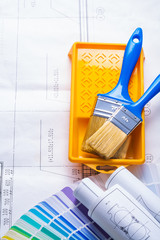 two paint brushes in tray on blueprints
