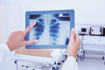 Composite image of doctor looking at xray on tablet