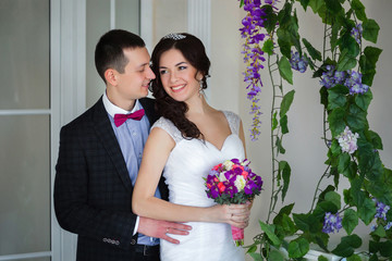 The groom embraces the bride, close to the vine