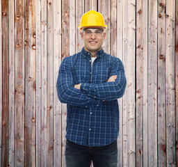 smiling male builder or manual worker in helmet