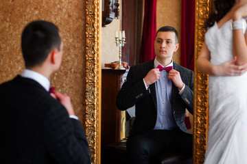 Bridegroom looks in the mirror and corrects butterfly