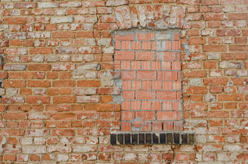 window closed with bricks in an old grungy brick wall