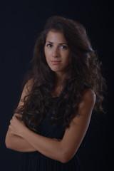 brunette girl with long hair in black dress smiling