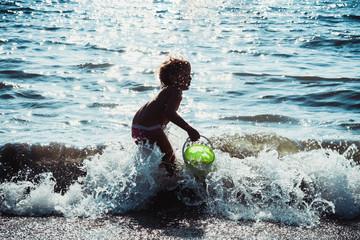 bambina a divertirsi al mare