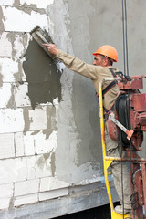 Construction  worker plastering multi storey building wall