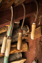 Set of various old rusty sickles, hanging in a shed