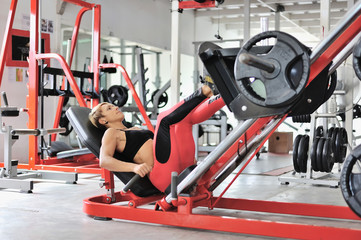 Fit woman training legs on a leg simulator at the gym