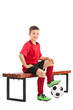 Junior football player sitting on a bench