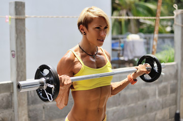 Athletic young woman doing workout with barbell outdoor