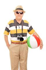 Mature tourist holding a beach ball