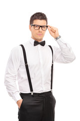 Elegant guy holding his glasses and looking at the camera