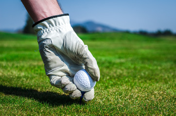 Hand with a glove is placing a tee with golf ball in the ground.