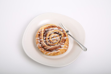 Cinnamon Roll on White Plate and Counter